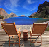 Two folding wooden chairs and the mountain lake Stock Image