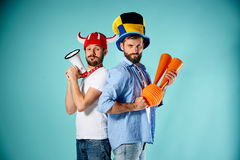 The two football fans with mouthpiece over blue stock image