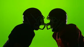 Two football helmets facing athlete in action. Green screen. Slow motion stock video