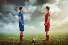 Two football player facing each other. On the kickoff at the stadium royalty free stock image