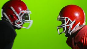 Two football players face helmets on the field. Green screen. Close up. Two football players in riot gear faced their helmets on the field. Green screen. Close stock video