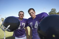 Two Football Players Holding Helmets Royalty Free Stock Images