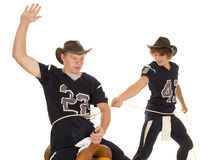 Two football players playing with a rope and saddle Royalty Free Stock Images