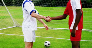 Two football players shaking hands. In the field stock video