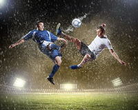 Two football players striking the ball Stock Images