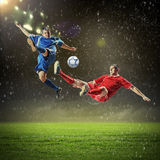 Two football players striking the ball Stock Photo