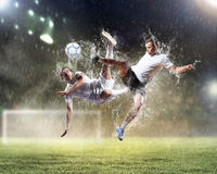 Two football players striking the ball. Two football players in jump to strike the ball at the stadium Stock Image