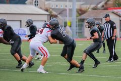 Two Football Players Tackle Each Other At A High School Game. Two high school football players tackle each other royalty free stock photography