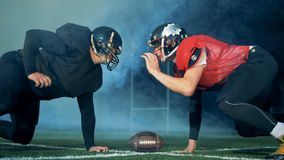 Two footballers are freezing in front of each other while playing american football. stock footage