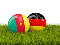 Two footballs with flags of Cameroon and Germany on green grass Royalty Free Stock Photo
