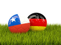 Two footballs with flags of Chile and Germany on green grass Stock Photos