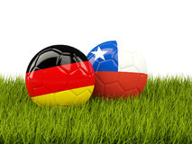 Two footballs with flags of Germany and Chile on green grass Stock Photos