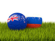 Two footballs with flags of New Zealand and Russia on green grass Royalty Free Stock Image