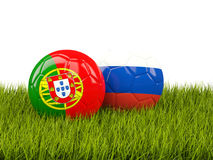 Two footballs with flags of Portugal and Russia on green grass Stock Photography
