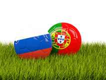 Two footballs with flags of Russia and Portugal on green grass Stock Photos