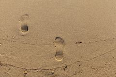 Two footprint in send on beach. Close up Stock Photos
