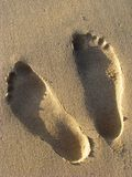 Two footprints in the sand. Foot prints in the beach sand showing the detail of the feet Royalty Free Stock Images