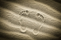 Two footprints in sand on the desert beach Stock Photos