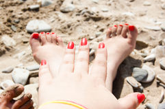 Two foots and one arm on the beach Stock Images