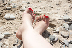 Two foots and one arm on the beach Royalty Free Stock Images