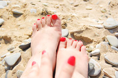 Two foots and one arm on the beach Stock Photo