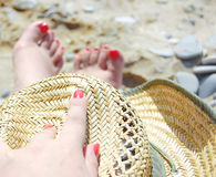 Two foots and one arm on the beach with hat Royalty Free Stock Photos
