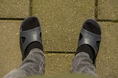Two foots of a person in socks in flip flops. Black socks standing on stone floor. royalty free stock photos