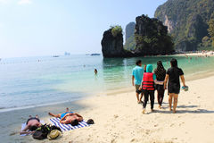 Two foreigners sunbathing and Thai tourist goup walk. Sea side, Thailand Royalty Free Stock Images
