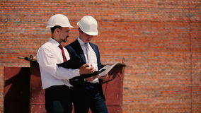 Two foreman at the construction discuss problem. Two foreman at the construction discuss the problem. The foremen holding a documents in hands and looking on it stock video