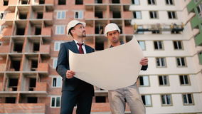 Two foreman looking building plan. Two foremen looking at the building plan. The men looking at the house and talking stock video
