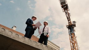 Two foreman talking on a sky background. The foremen are holding a documents in the hands and discussing the problem stock footage