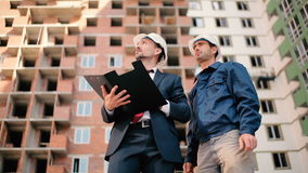 Two foremen discuss the building plan. The man hold in the hand a folder with documents. Two foremen are talking and discussing the building around him stock video