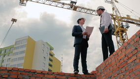 Two foremen discuss the building project stock video footage