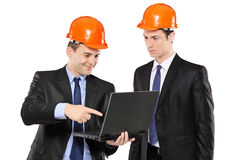 Two foremen looking at laptop. Isolated on white background Stock Photos
