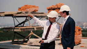 Two foremen are talking near the construction stock footage