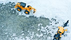 Two forklifts on snow and ice covered roads. Toy truck, Winter snow, Cement floor Stock Photography