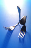 Two forks bent on blue background Royalty Free Stock Photos