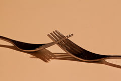 Two forks entangled in low light Royalty Free Stock Images