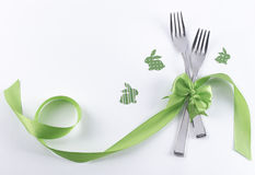 Two forks with green bunnies and ribbon. Silverware for celebration kid's party on white background Stock Image