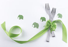 Two forks with green elephants and decoration. Silverware on white with green ribbon as background for menu and invitation Stock Image