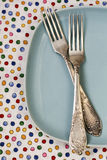 Two forks lying on blue plate on bright background. Two forks lying on blue plate on background Royalty Free Stock Photo