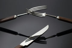 Two forks nad knife. Brightly lit forks and knife on a dark background Stock Photo