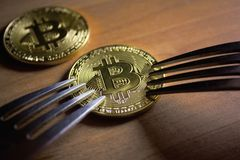 Two forks next to coin of bitcoin. Two forks rest on a bitcoin coin Stock Photography