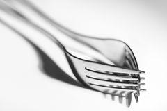 Two forks with shadow on white background stock photos