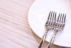 Two forks. On a white plate Stock Photos