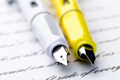 Two fountain pens on a letter.  stock images