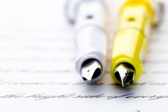 Two fountain pens on a letter.  stock photo
