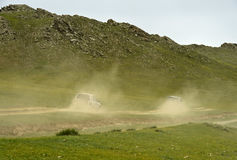 Two four-wheel-drive vehicles with tourists on a dusty dirt road Stock Image