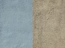 Wall are covered with blue and yellow textured plaster. Two fragments of the house wall are covered with blue and yellow textured plaster royalty free stock photography