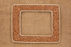 Two frame made of rope with buckwheat grains on sackcloth Stock Photography